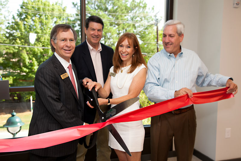 Jack Halpern, Mayor Rusty Paul, Carolyn Oppenheimer, and Councilman Andy Bauman smile as they cut a large red ribbon
